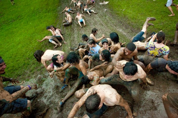 Festival-goers slide down a muddy hillside